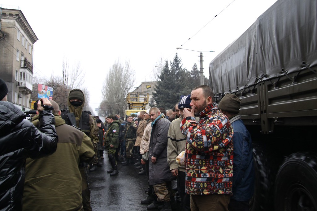 Description of . Captive Ukrainian soldiers stand as they are paraded at a bus stop where 13 people were killed in a trolleybus shelling in Donetsk, eastern Ukraine, on January 22, 2015. At least 41 people were killed in Ukraine's east on January 22, one of the deadliest days in the separatist war, with a bloody bus shelling in Donetsk as government forces abandoned their defense of the city's strategic airport. In a graphic illustration of the degenerating nine-month conflict, pro-Russian rebels also paraded some 20 captured Ukrainian soldiers through Donetsk and forced them to kneel before enraged locals who threw snowballs and glass at them, some of it from the shattered bus. ALEKSANDER GAYUK/AFP/Getty Images