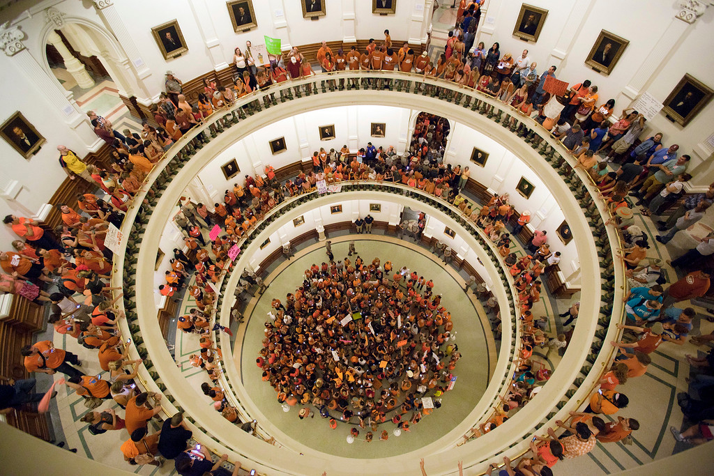 Description of . Abortion rights advocates fill the rotunda of the State Capitol as the Senate nears the vote on Friday night, July 12, 2013. Texas senators were wrapping up debate on sweeping abortion restrictions Friday night and were poised to vote on a measure after weeks of protests. (AP Photo/Tamir Kalifa)