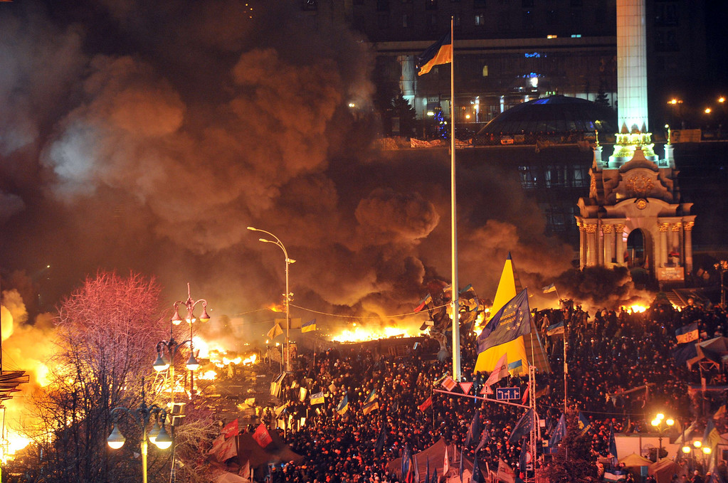 Description of . Anti-government protesters clash with the police during their storming of the Independence Square in Kiev on February 18, 2014. Flames engulfed the main anti-government protest camp on Kiev's Independence Square on Tuesday as riot police tried to force demonstrators out following the bloodiest clashes in three months of protests. The iconic square turned into a war zone as riot police moved slowly through opposition barricades from several directions, hurling stun grenades and using water cannon to clear protestors.  AFP PHOTO/ GENYA SAVILOV/AFP/Getty Images
