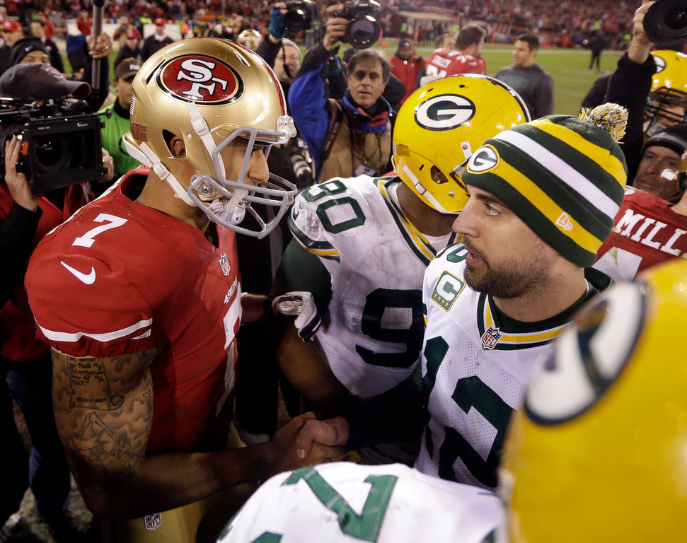 Description of . San Francisco 49ers quarterback Colin Kaepernick (7) talks with Green Bay Packers quarterback Aaron Rodgers (12) after an NFC divisional playoff NFL football game in San Francisco, Saturday, Jan. 12, 2013. The 49ers won 45-31. (AP Photo/Marcio Jose Sanchez)