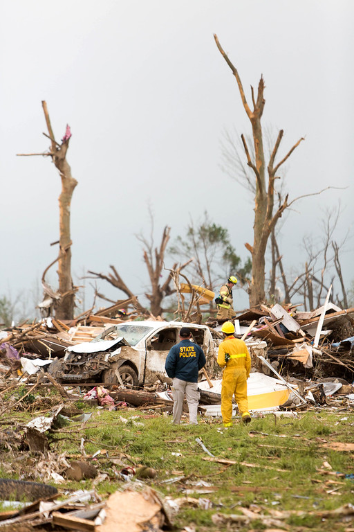 Description of . Police and fire officials search for survivors in what's left of a home on Cemetery Street in Vilonia, Ark., Monday, April 28, 2014 after a tornado struck the town late Sunday.   (AP Photo/Karen E. Segrave)