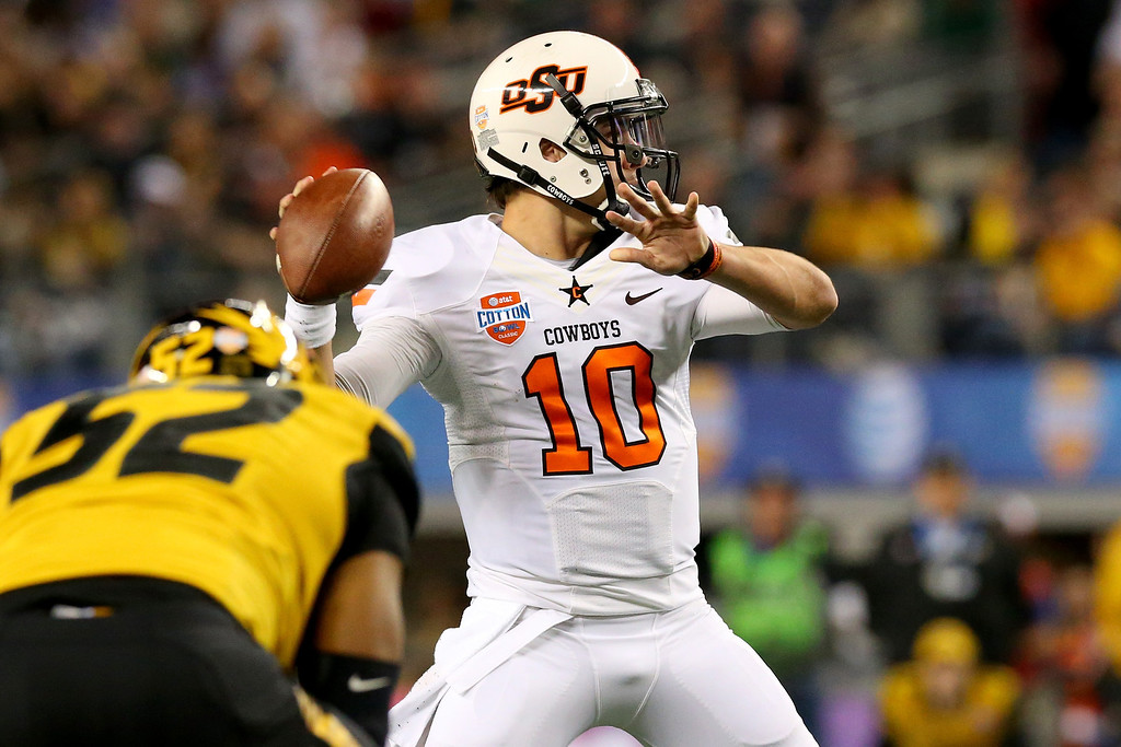 Description of . ARLINGTON, TX - JANUARY 03:  Quarterback Clint Chelf #10 of the Oklahoma State Cowboys passes in the first half as Michael Sam #52 of the Missouri Tigers rushes in during the AT&T Cotton Bowl on January 3, 2014 in Arlington, Texas.  (Photo by Ronald Martinez/Getty Images)