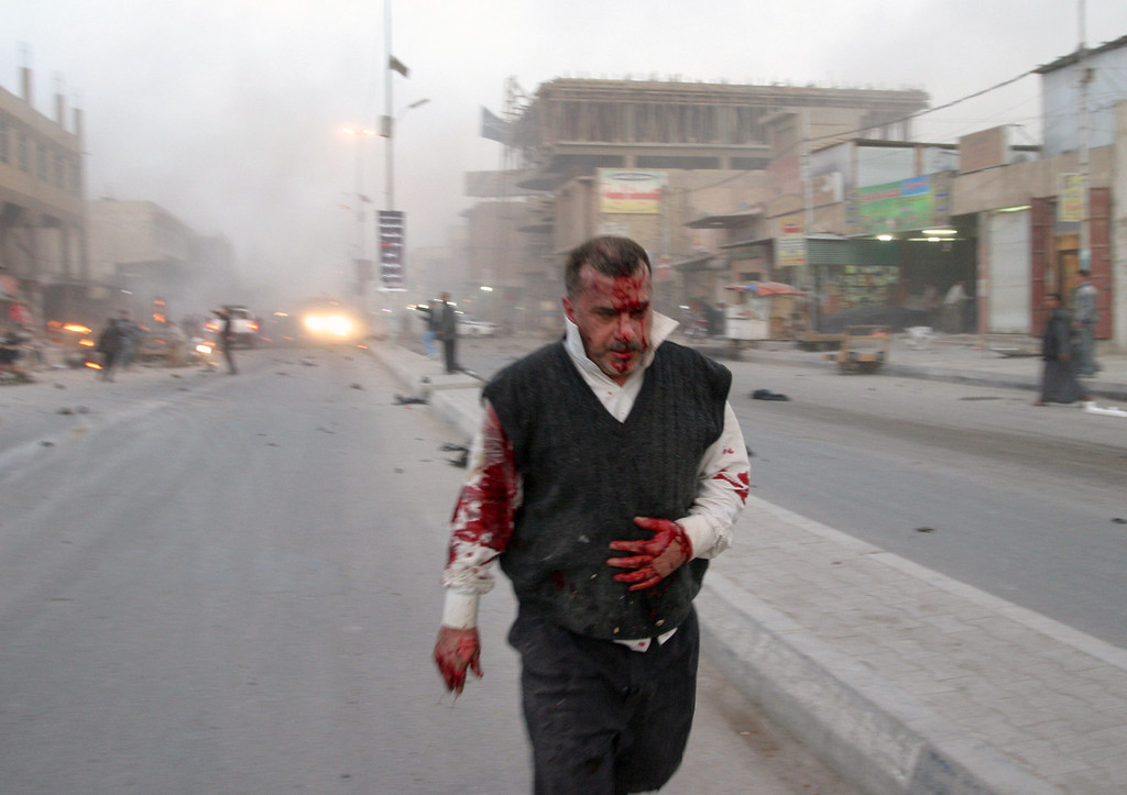 Description of . A wounded man is seen after a bombing in Najaf, 100 miles (160 kilometers) south of Baghdad, Iraq, Thursday, Jan. 14, 2010.  Three explosions, including one caused by a car bomb, rocked the southern city of Najaf at about 5:45 p.m. near a commercial area, police said. An official in the city\'s health department said at least one person was killed and 50 were wounded. (AP Photo/Alaa al-Marjani)