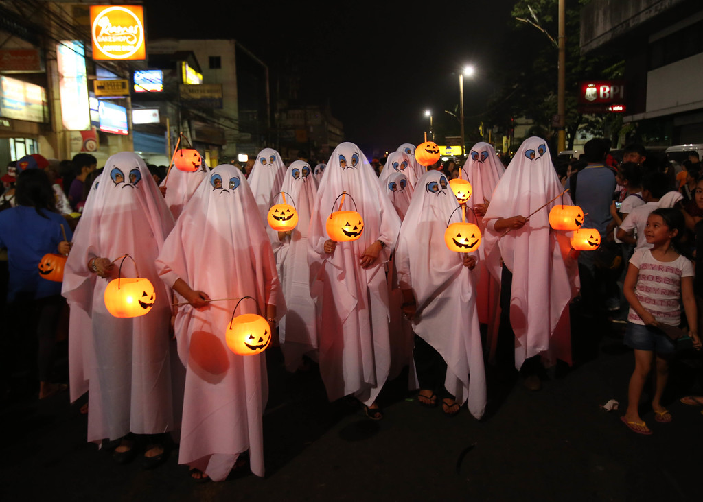 Description of . Filipinos wear ghost costumes as they join a Halloween Parade in Marikina city, east of Manila, Philippines on Wednesday, Oct. 30, 2013. Hundreds of residents and government employees joined the parade as the country prepares to observe All Saints Day on Nov. 1. (AP Photo/Aaron Favila)