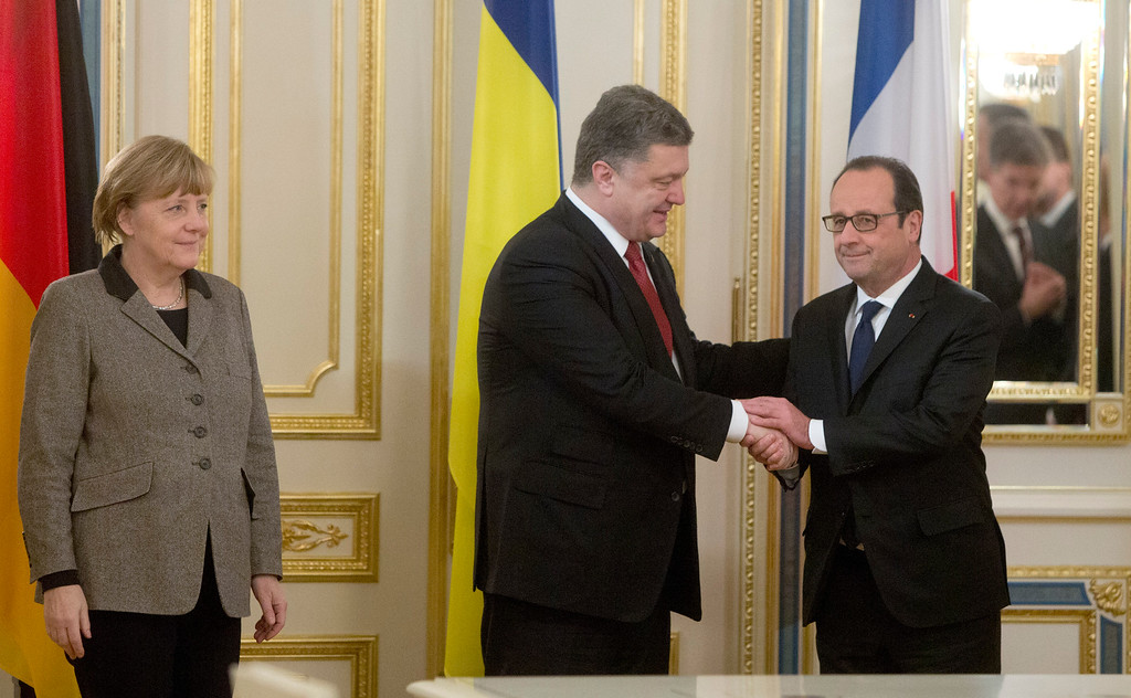 Description of . Ukrainian President Petro Poroshenko, center, shakes hands with French President Francois Hollande, right, and German chancellor Angela Merkel during their meeting in Kiev, Ukraine, Thursday, Feb. 5, 2015. The leaders of France and Germany were carrying a new peace initiative to the Ukrainian and Russian capitals Thursday, amid a flurry of high-level diplomacy to end what Hollande called a war on Europe's edge. (AP Photo/Efrem Lukatsky)