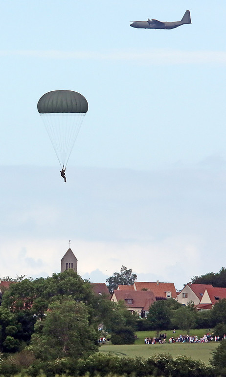 Description of . A paratrooper prepares to land in the fields near Ranville western France, Thursday June 5, 2014, as part of the commemoration of the 70th anniversary of the D Day. (AP Photo/Remy de la Mauviniere)