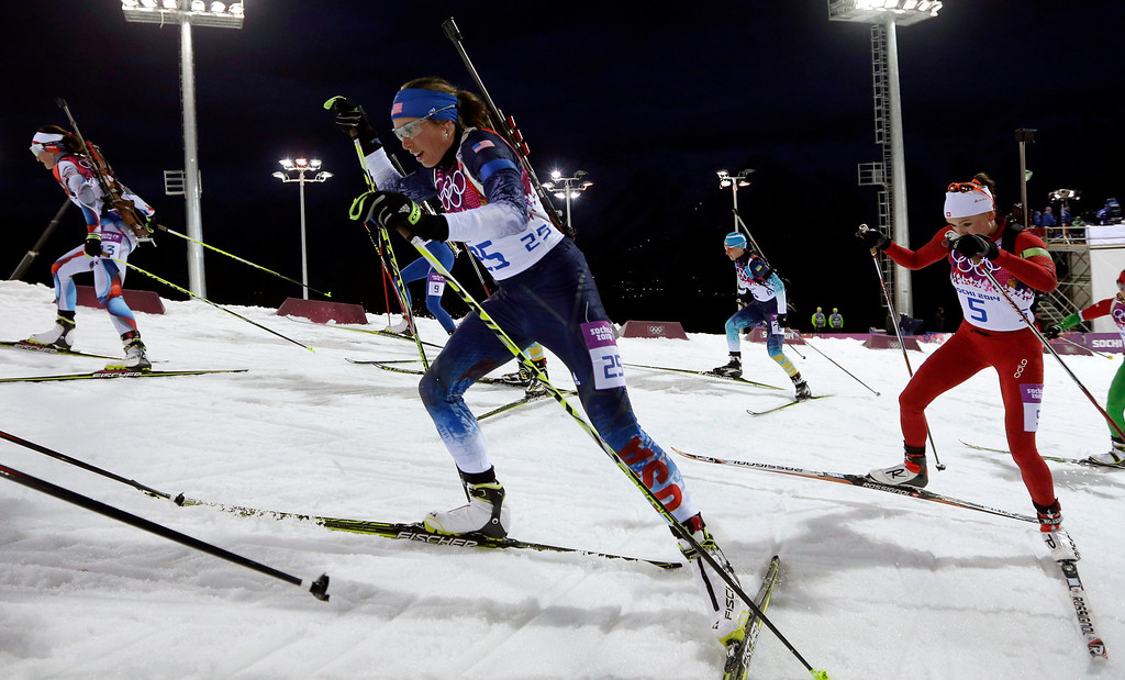 Description of . United States' Susan Dunklee, center, leads Switzerland's Selina Gasparin as she competes in the women's biathlon 12.5k mass-start, at the 2014 Winter Olympics, Monday, Feb. 17, 2014, in Krasnaya Polyana, Russia. (AP Photo/Felipe Dana)