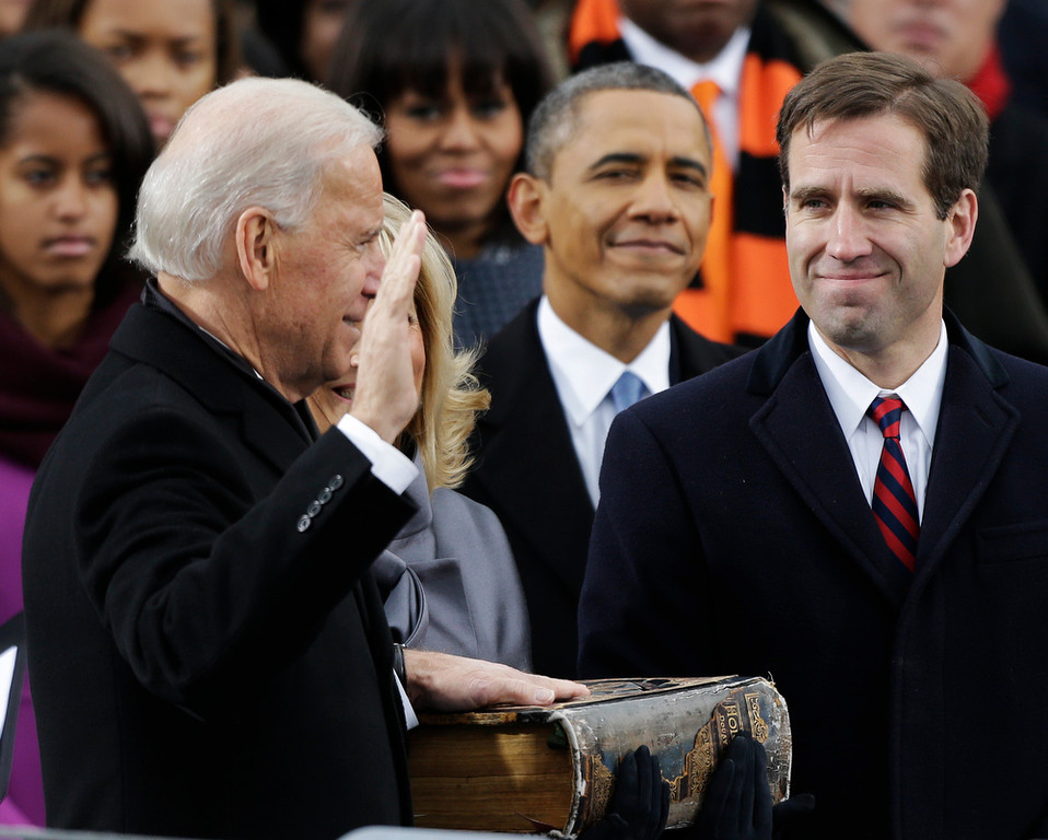 Description of . President Barack Obama, center and Beau Biden, Attorney of Deleware, right, watch as his father Joe Biden is sworn in at the ceremonial swearing-in at the U.S. Capitol during the 57th Presidential Inauguration in Washington, Monday, Jan. 21, 2013. (AP Photo/Pablo Martinez Monsivais)