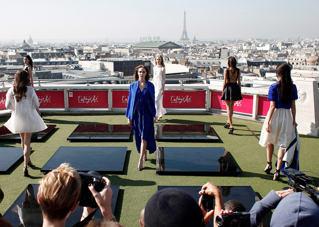 Description of . Models present creations as part of French fashion designer Christine Phung's ready-to-wear Spring/Summer 2014 fashion collection presented in Paris, Tuesday, Sept.24, 2013. The Eiffel Tower is seen in background. (AP Photo/Thibault Camus)