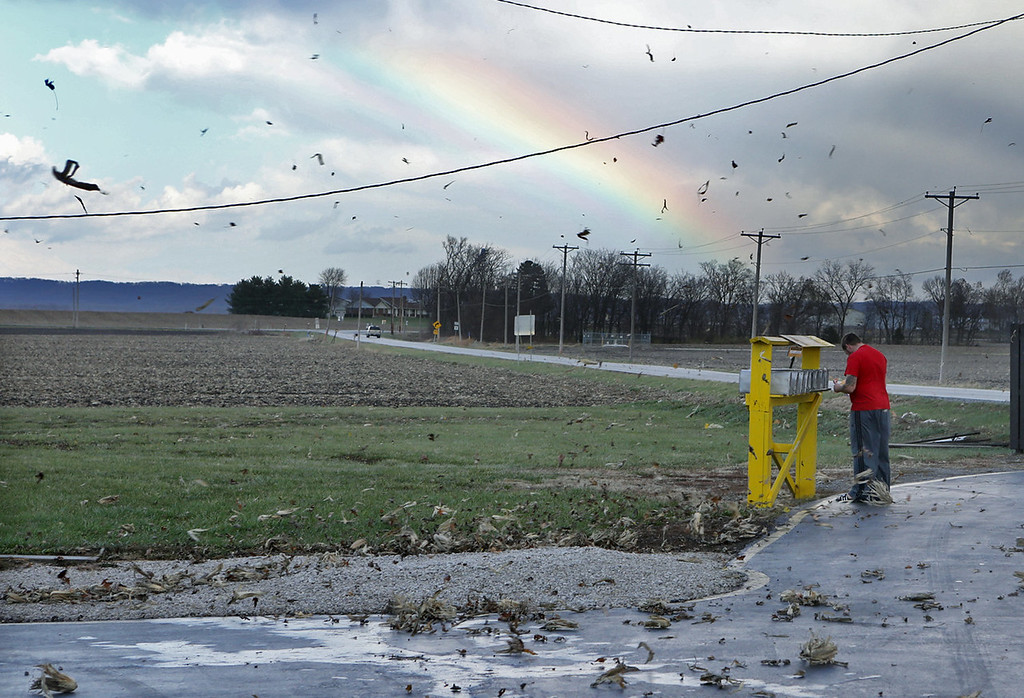 Description of . Eric Crawford, 28, waited for the storm to pass and a rainbow to appear before checking on his mail in rural Orchard Farm on Sunday, Nov. 17, 2013, in St. Charles County. Corn husks were flying through the air in the high winds. (AP Photo/St. Louis Post-Dispatch,  J.B. Forbes)
