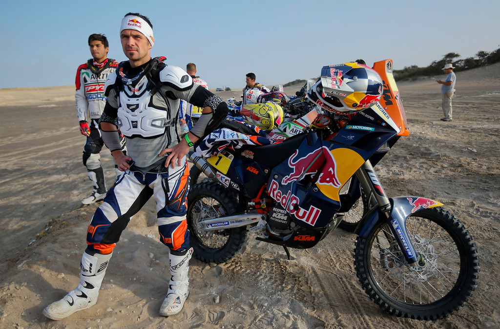Description of . KTM rider Cyril Despres, center, and KTM rider Andre Hirioyen, left, both of France, wait  for the start of the 3nd stage of the 2013 Dakar Rally from Pisco to Nazca, Peru, Monday, Jan. 7, 2013. The race finishes in Santiago, Chile, on Jan. 20. (AP Photo/Victor R. Caivano)