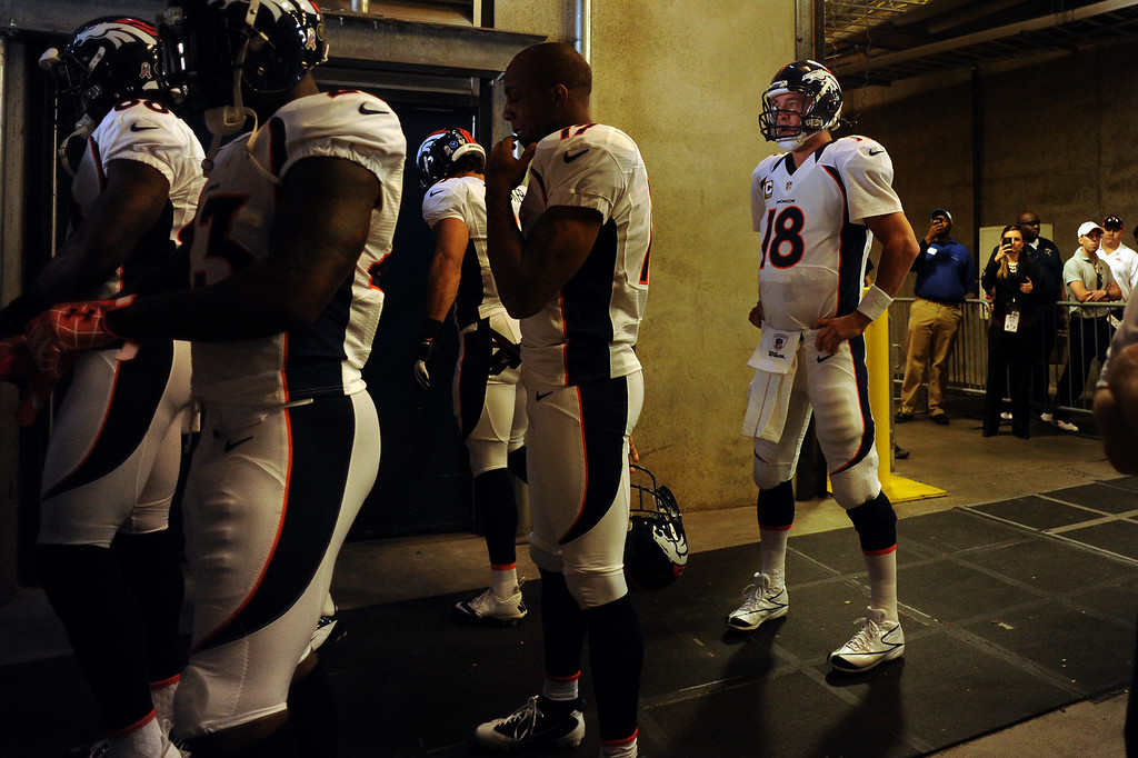 Description of . Denver Broncos quarterback Peyton Manning #18 waiting behind his team to take the field for the second half against the Carolina Panthers at Bank of America Stadium in Charlotte, North Carolina  November 11th, 2012.      Joe Amon, The Denver Post
