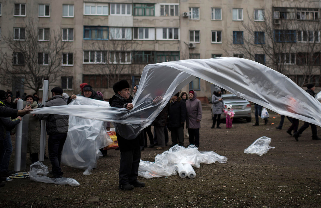 Description of . Local residents prepare plastic sheeting to cover broken windows near heating tents after Saturday's shelling at Vostochniy district of Mariupol, Ukraine, Monday, Jan. 26, 2015. At least 5,100 people have been killed in eastern Ukraine since fighting began in April 2014, but violence this week was the most intense since a cease-fire deal was signed in September. (AP Photo/Evgeniy Maloletka)