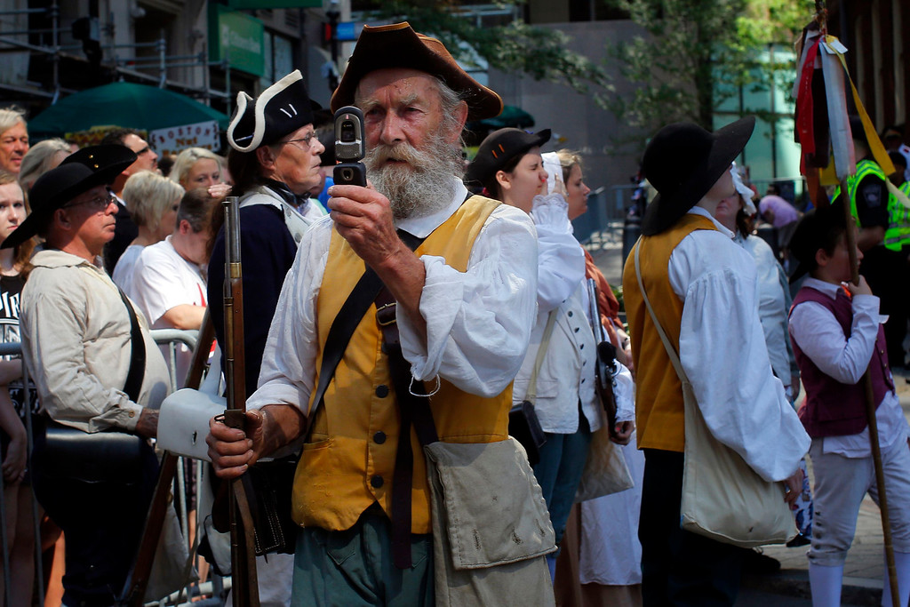 Description of . A re-enactor in period attire takes a photograph with his mobile phone before a public reading the United States Declaration of Independence, part of Fourth of July Independence Day celebrations, in Boston, Massachusetts July 4, 2013. People across the United States gathered on Thursday for parades, picnics and fireworks at Independence Day celebrations, held under unprecedented security following the Boston Marathon bombings. Spectators waving U.S. flags and wearing red, white and blue headed for public gatherings in Boston, New York, Washington, Atlanta and other cities under the close watch of police armed with hand-held chemical detectors, radiation scanners and camera surveillance, precautions sparked by the deadly April 15 bombings.     REUTERS/Brian Snyder