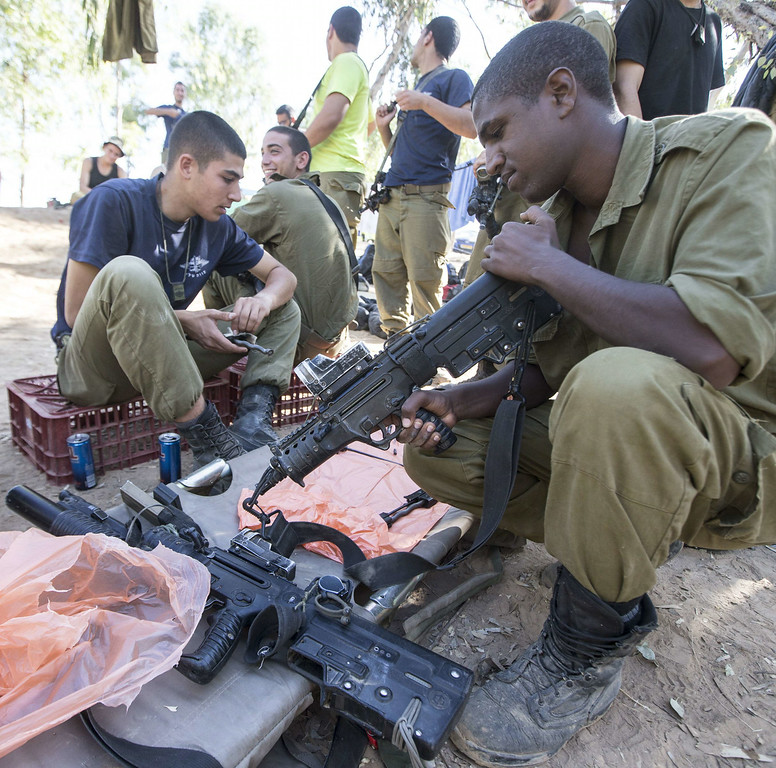 Description of . Israeli soldiers from an Infantry Brigade clean their weapons at an army deployment area near Israel's border with the Gaza Strip, on July 16, 2014. New Israeli air and tank strikes in Gaza killed several people, medics said, bringing the death toll from Israel's operation in the besieged Palestinian territory to 208. Since the latest violence began before dawn on July 8, 990 rockets fired from Gaza have struck Israel, and another 244 have been shot down by the Iron Dome anti-missile system, army figures show.  AFP PHOTO / JACK GUEZ/AFP/Getty Images