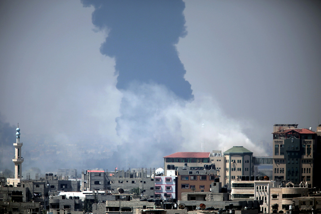 Description of . Smoke rises from an Israeli strike at a building in Gaza City, foreground, as black smoke billows from Gaza's electricity distribution company, background, after it was hit earlier by Israeli strikes in the Nusayrat refugee camp, central Gaza Strip, Tuesday, July 29, 2014. (AP Photo/Khalil Hamra)