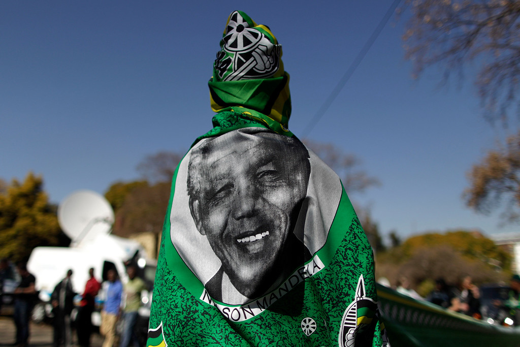 Description of . A vendor wearing a shawl bearing the image of former South African President Nelson Mandela at the entrance to the Mediclinic Heart Hospital where Nelson Mandela is being treated in Pretoria, South Africa Friday, June 28, 2013. Members of Nelson Mandela's family as well as South African Cabinet ministers have visited the hospital on Friday where the 94-year-old former president is critically ill. (AP Photo/Muhammed Muheisen)