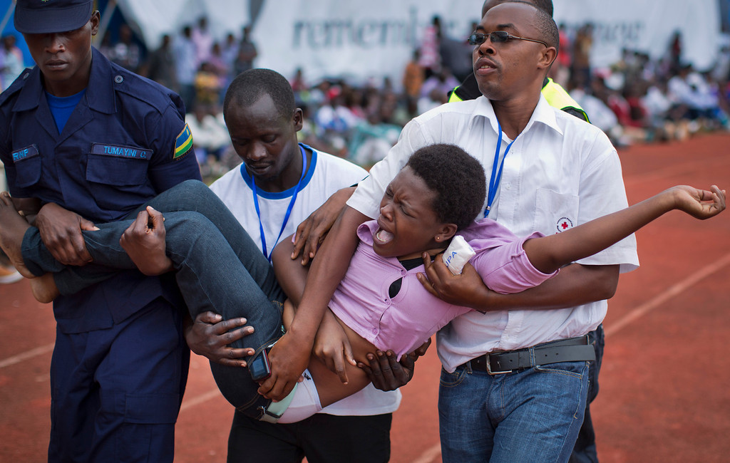 Description of . A wailing and distraught Rwandan woman, one of dozens overcome by grief at recalling the horror of the genocide, is carried away to receive help during a public ceremony to mark the 20th anniversary of the Rwandan genocide, at Amahoro stadium in Kigali, Rwanda Monday, April 7, 2014. Sorrowful wails and uncontrollable sobs resounded Monday as thousands of Rwandans packed the country's main sports stadium to mark the 20th anniversary of the beginning of a devastating 100-day genocide. (AP Photo/Ben Curtis)