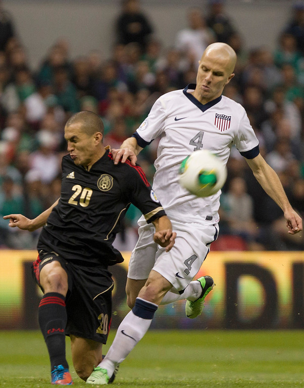 Description of . Jorge Torres (#20) of Mexico fights for the ball with Michael Bradley (#4) of the United States during a match between Mexico and US as part of FIFA 2014 World Cup Qualifier at The Azteca stadium on March 26, 2013 in Mexico City, Mexico. (Photo by Miguel Tovar/Getty Images)
