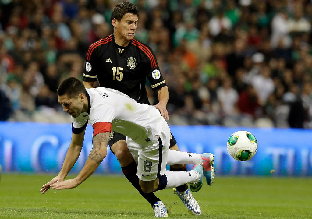 Description of . United States captain Clint Dempsey, left, is tackled by Mexico's Hector Moreno during a 2014 World Cup qualifying match at the Aztec stadium in Mexico City, Tuesday, March 26, 2013. (AP Photo/Eduardo Verdugo)