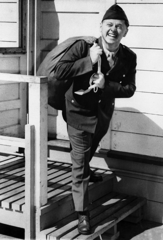 Description of . Flashing the same smile known to millions of film-goers, Mickey Rooney, 22, year-old film star, steps from the induction station at Fort MacArthur, Los Angeles, California, on June 26, 1944, wearing an army uniform and carrying a duffel bag over his shoulder. ? (AP Photo)