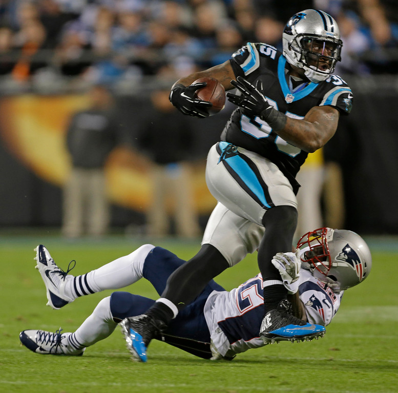 . Carolina Panthers\' Mike Tolbert, top, is tackled by New England Patriots\' Devin McCourty, bottom, during the second half of an NFL football game in Charlotte, N.C., Monday, Nov. 18, 2013. (AP Photo/Bob Leverone)