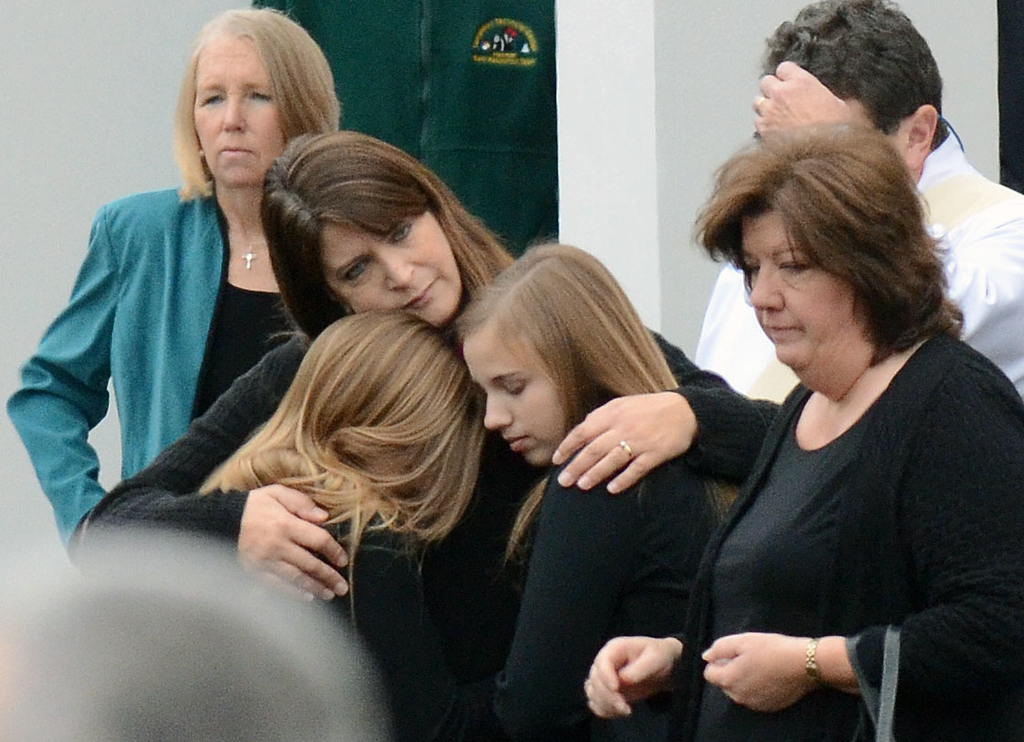 Description of . Staff photos by Tom Kelly IV Family members of Jessica Rekos, console one another after the funeral, on the front steps of the church.  Funerals for two, six year old students from the Sandy Hook Elementary School in Newtown, CT took part Tuesday December 18, 2012.  Mourners paid their respects at the Saint Rose of Lima Church.