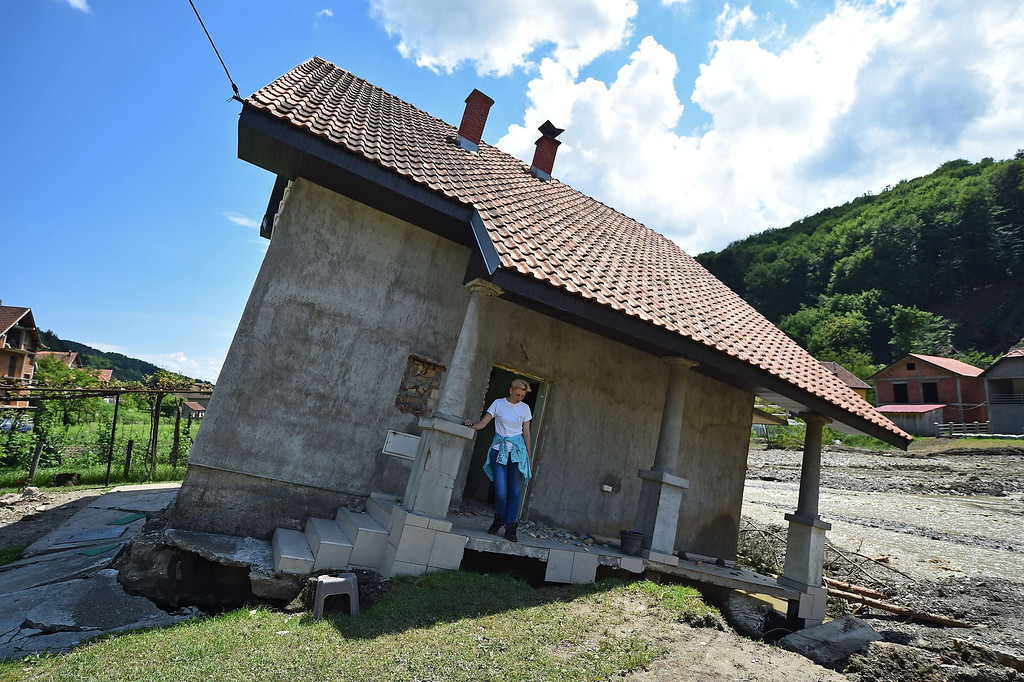 Description of . Flood victim Pavlovic Oksana stands on the front porch of her house, damaged by flooding and landslide, in Krupanj, some 130 kilometers south west of Belgrade, on May 20, 2014, after the western Serbian town was hit with floods and landslides, cutting it off for four days. Serbia declared three days of national mourning on May 20 as the death toll from the worst flood to hit the Balkans in living memory rose and health officials warned of a possible epidemic.   AFP PHOTO / ANDREJ ISAKOVIC/AFP/Getty Images