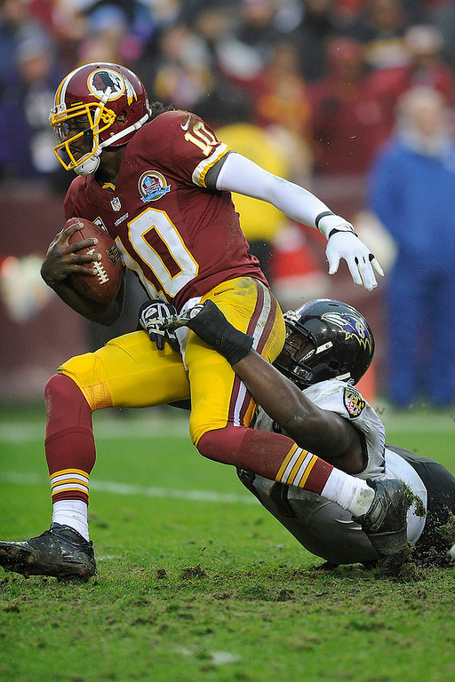 Description of . Baltimore Ravens defensive end Arthur Jones pulls Washington Redskins quarterback Robert Griffin III to the ground during the second half of an NFL football game in Landover, Md., Sunday, Dec. 9, 2012. (AP Photo/Nick Wass)