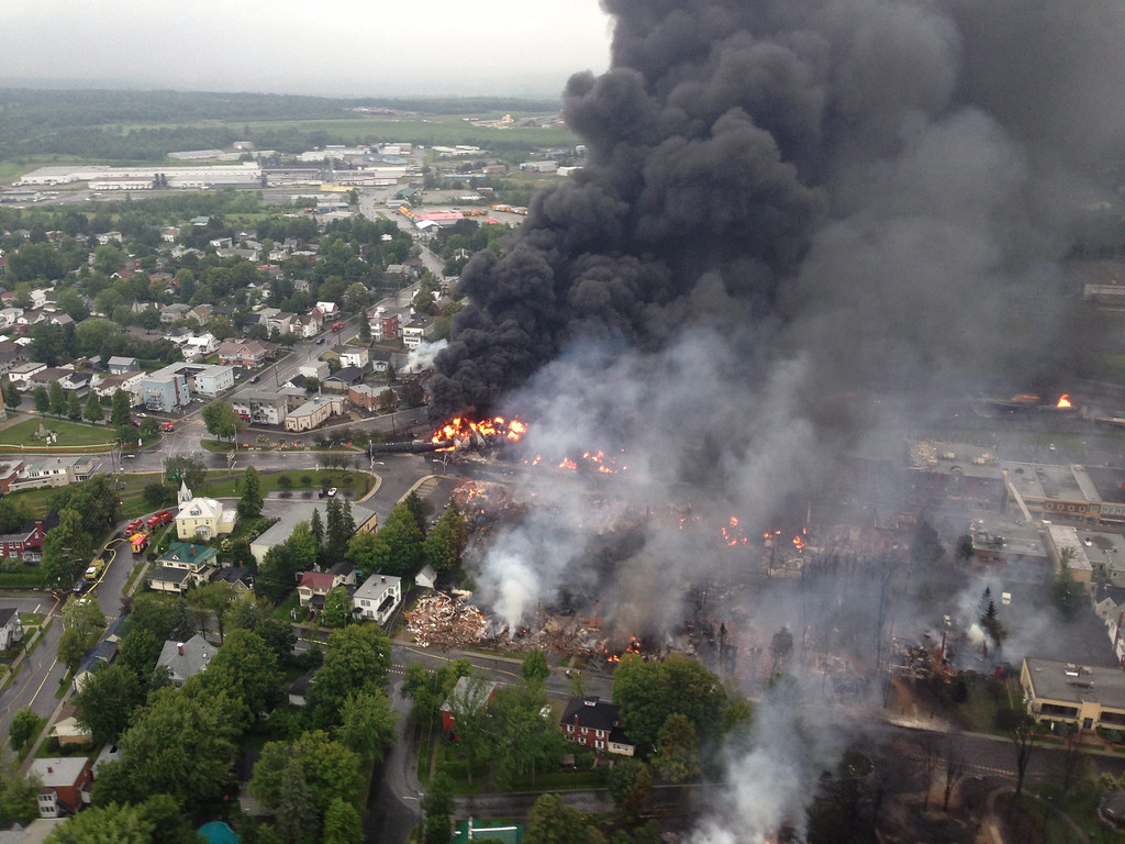 Description of . An aerial view of a fire in the town of Lac-Megantic is seen from a S˚retÈ du QuÈbec helicopter Saturday, July 6, 2014 following a train derailment the sparked several explosions in Lac Megantic, Quebec. (AP Photo/S˚retÈ du QuÈbec via The Canadian Press)