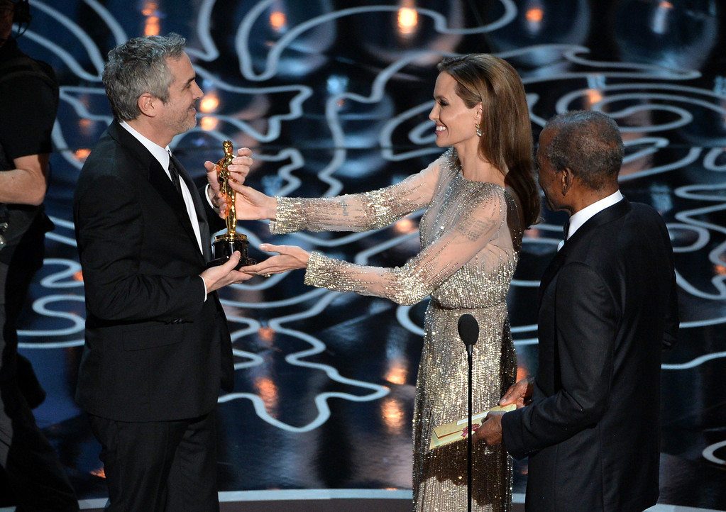 Description of . (L-R) Director Alfonso Cuaron accepts the Best Achievement in Directing award for 'Gravity' from actors Angelina Jolie and Sidney Poitier onstage during the Oscars at the Dolby Theatre on March 2, 2014 in Hollywood, California.  (Photo by Kevin Winter/Getty Images)