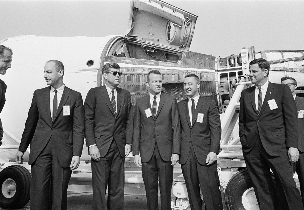 Description of . Kennedy poses with astronauts L. Gordon Cooper, center, and Gus Grissom during a tour of Cape Canaveral, Fla., on Nov. 16, 1963. The astronauts briefed Kennedy on the Gemini two-man spacecraft, a mock-up of which is in the background. The others are unidentified.  Associated Press file