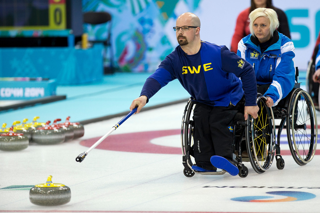 Description of . Sweden's Kicki Ulander, right, steadies the chair of Patrik Kallin during round robin session wheelchair curling match against Canada at the 2014 Winter Paralympics in Sochi, Russia, Sunday, March 9, 2014. Canada won 7-4. (AP Photo/Pavel Golovkin)