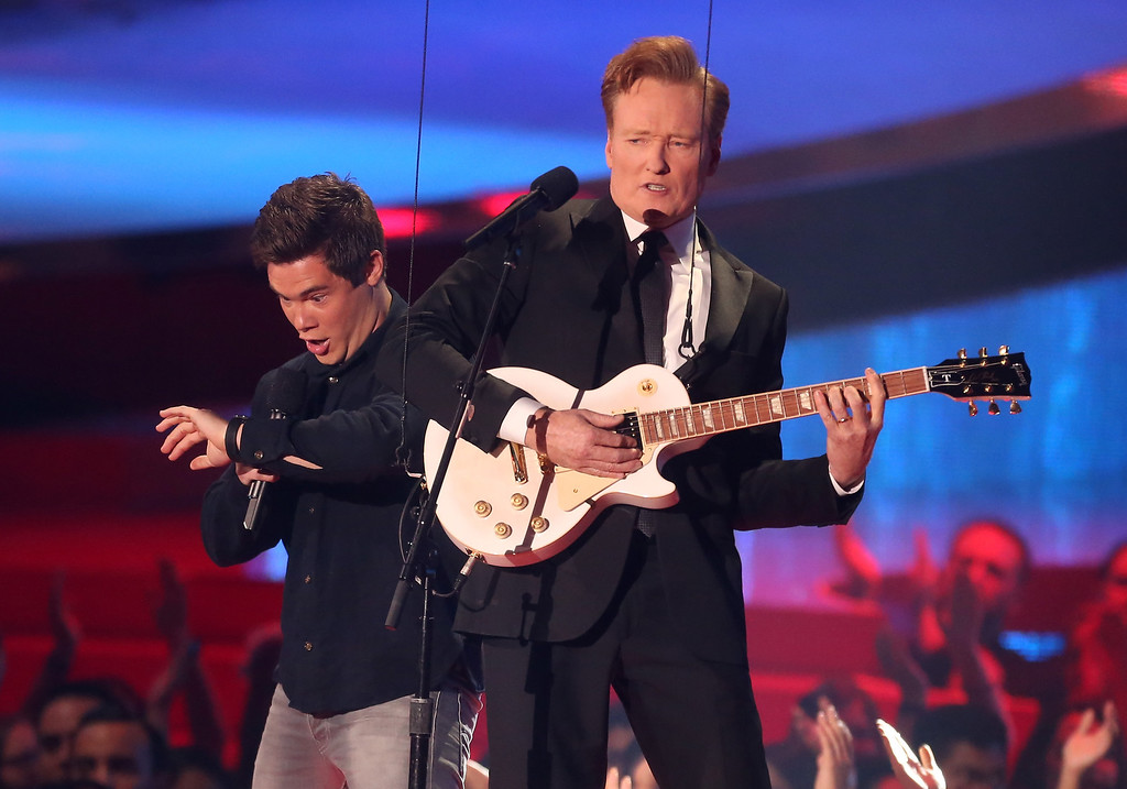 Description of . Actor Adam DeVine (L) and host Conan O'Brien perform onstage at the 2014 MTV Movie Awards at Nokia Theatre L.A. Live on April 13, 2014 in Los Angeles, California.  (Photo by Frederick M. Brown/Getty Images)