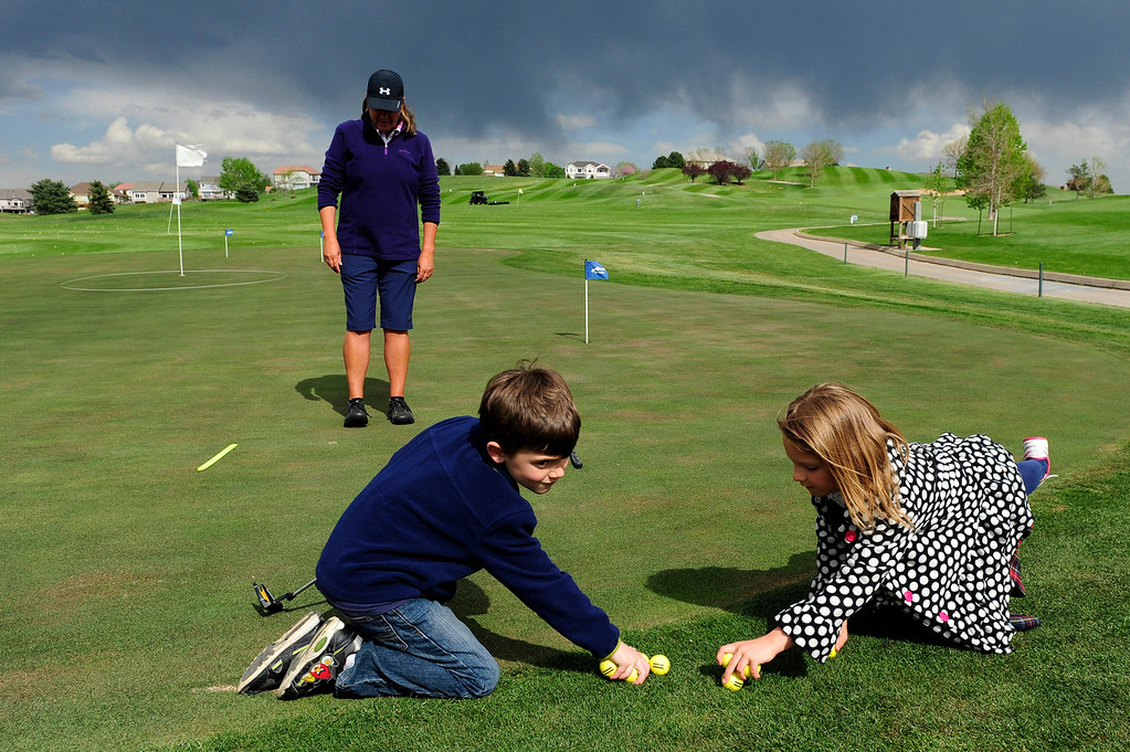 Description of . DENVER, CO - MAY 7: Eva Hellvig, 7, right, and Cameron Fay, 6, collect their golf balls during their first class with Nina Krats, seen in the background, at Foothills Golf Course on May 7, 2014, in Denver, Colorado. Foothills Park and Recreation is aiming to increase participation in its golf programs, especially in regards to youth involvement. (Photo by Anya Semenoff/The Denver Post)