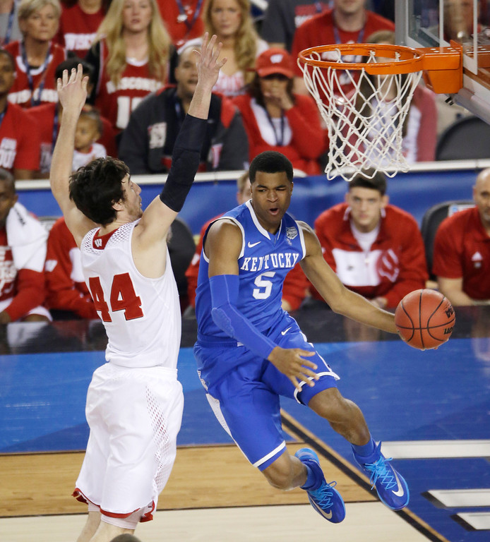 Description of . Kentucky guard Andrew Harrison, right, drives past Wisconsin forward Frank Kaminsky, left, during the first half of an NCAA Final Four tournament college basketball semifinal game Saturday, April 5, 2014, in Arlington, Texas. (AP Photo/Tony Gutierrez)
