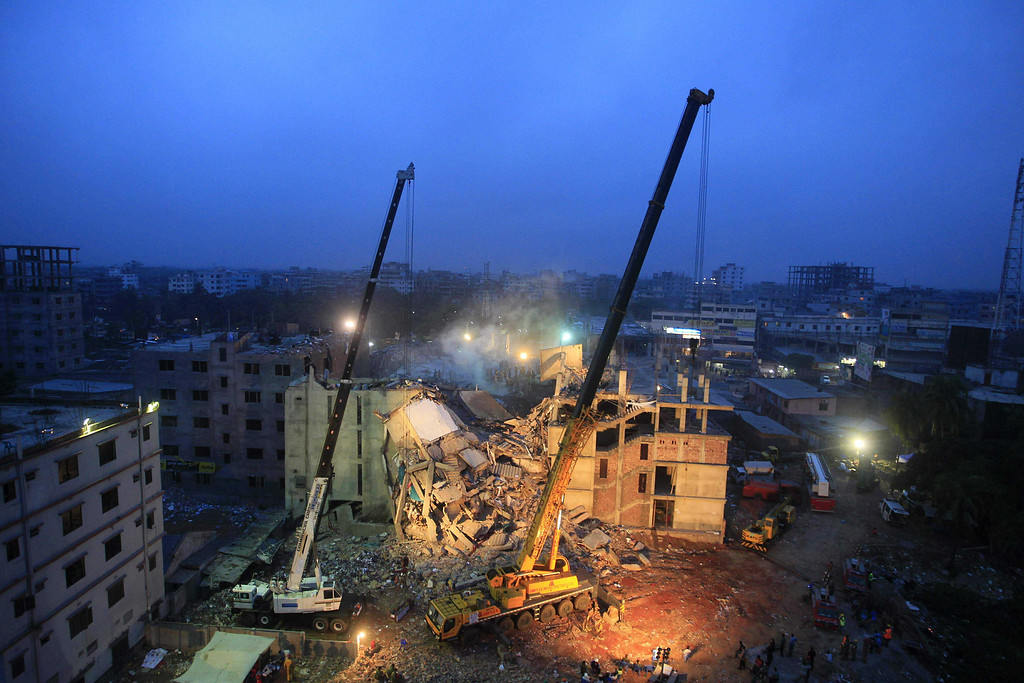 Description of . Cranes operated by Bangladeshi Army personnel work at the scene of the April 24 collapse of an eight-story building in Savar, on the outskirts of Dhaka, on April 29, 2013.  Bangladeshi textile bosses pleaded April 29 with Western clothing giants to keep doing business with them after nearly 400 people died in a factory collapse as hopes of finding more survivors faded. The factory caved in while some 3,000 textile workers were on shift.  STRDEL/AFP/Getty Images