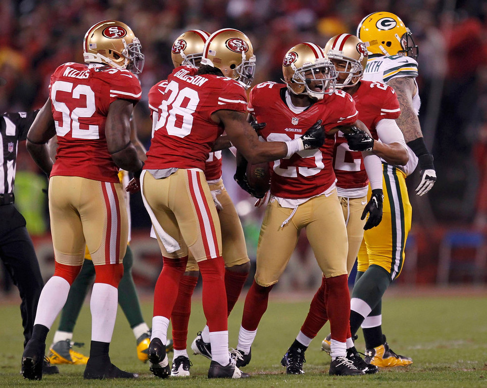 Description of . San Francisco 49ers Tarrell Brown (2nd R) celebrates with teammates Carlos Rogers (R), Patrick Willis (L) and Dashon Goldson (2nd L) after intercepting a pass against the Green Bay Packers in the second quarter during their NFL NFC Divisional playoff football game in San Francisco, California, January 12, 2013.   REUTERS/Robert Galbraith