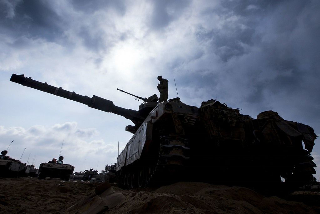 Description of . An Israeli soldier prepares a Merkava tank at an army deployment along the border between Israel and the Hamas-controlled Palestinian territory on July 29, 2014.  AFP PHOTO / JACK  GUEZ/AFP/Getty Images