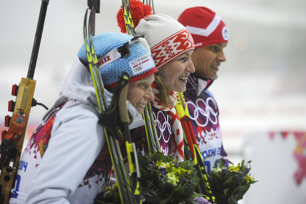 Description of . Silver medalist Norway\'s Tora Berger (L), gold medalist Belarus\' Darya Domracheva and bronze medalist Slovenia\'s Teja Gregorin celebrates on the podium during the Women\'s Biathlon 10 km Individual Flower Ceremony at the Laura Cross-Country Ski and Biathlon Center during the Sochi Winter Olympics on February 11, 2014 in Rosa Khutor near Sochi.  PIERRE-PHILIPPE MARCOU/AFP/Getty Images