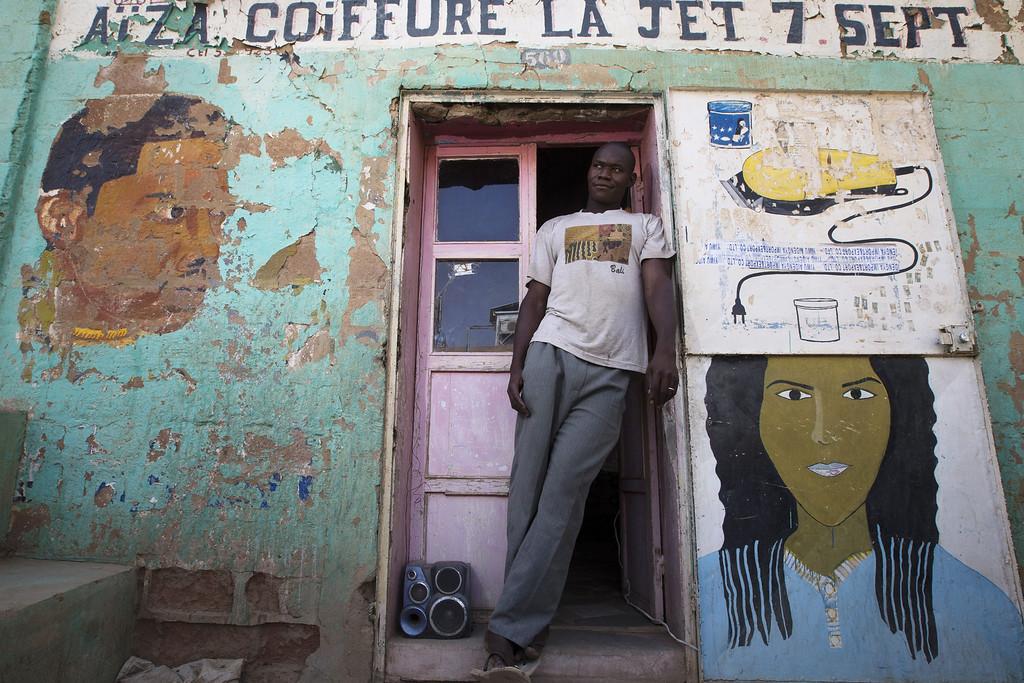 Description of . A hair dresser stands outside his shop in Gao on April 13, 2013.  JOEL SAGET/AFP/Getty Images