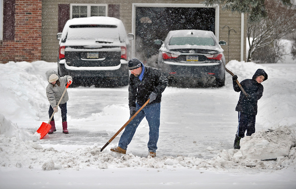 Description of . Simon Tack and his children Marissa, 7, left, and Johnny, 9, shovel snow out of their driveway along Saxton Drive, in State College, Pa. on Thursday, Feb. 13, 2014. A winter storm hit Centre County causing all local schools to close amid dangerous travel conditions. (AP Photo/Centre Daily Times, Nabil K. Mark)