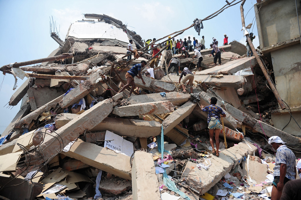 Description of . Bangladeshi volunteers and rescue workers are pictured at the scene after an eight-storey building collapsed in Savar, on the outskirts of Dhaka, on April 25, 2013.  AFP PHOTO/Munir uz ZAMAN/AFP/Getty Images