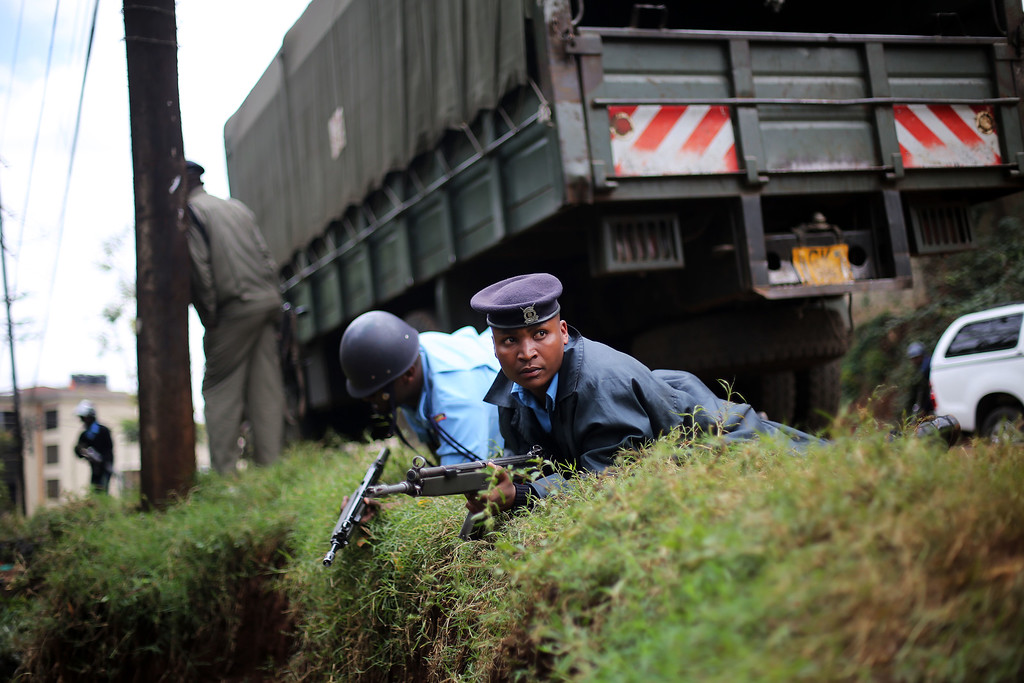 Description of . Kenyan security officers takes cover as gunfire and explosions are heard from the Westgate Mall in Nairobi Kenya Monday Sept. 23 2013. Multiple large blasts have rocked the mall where a hostage siege is in its third day.  (AP Photo/ Jerome Delay)