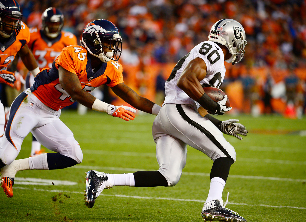 Description of . Denver Broncos cornerback Dominique Rodgers-Cromartie (45) closes in on Oakland Raiders wide receiver Rod Streater (80) in the first quarter. The Denver Broncos took on the Oakland Raiders at Sports Authority Field at Mile High in Denver on September 23, 2013. (Photo by Tim Rasmussen/The Denver Post)