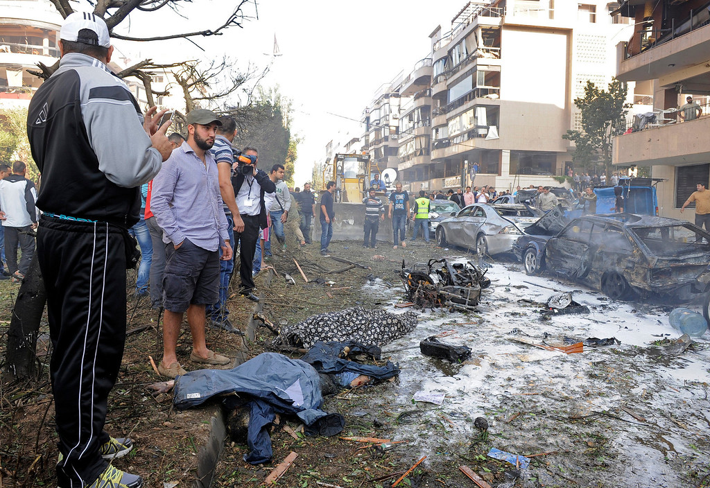 Description of . Two men stands over a dead bodies at the scene after a number of explosions near the Iranian embassy in Beirut, Lebanon, 19 November 2013. The death toll from a double suicide bombing near the Iranian embassy in Beirut has risen to 23, including at least two Iranian citizens, the Lebanese Health Ministry says and about 146 others were wounded.  EPA/WAEL HAMZEH