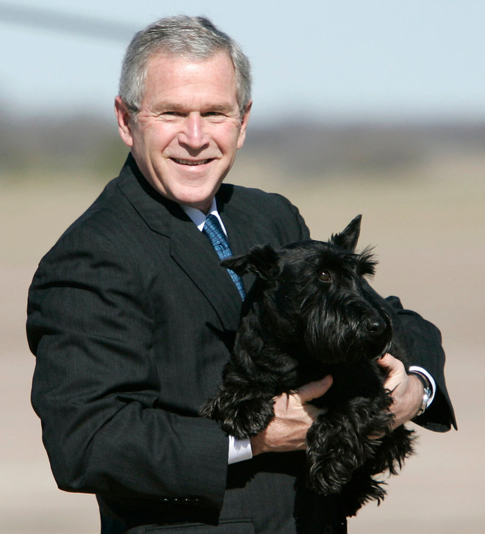 Description of . In this Dec. 26, 2006 file photo, President George W. Bush carries his dog Barney across the airport tarmac in Waco, Texas.  (AP Photo/Evan Vucci, File)