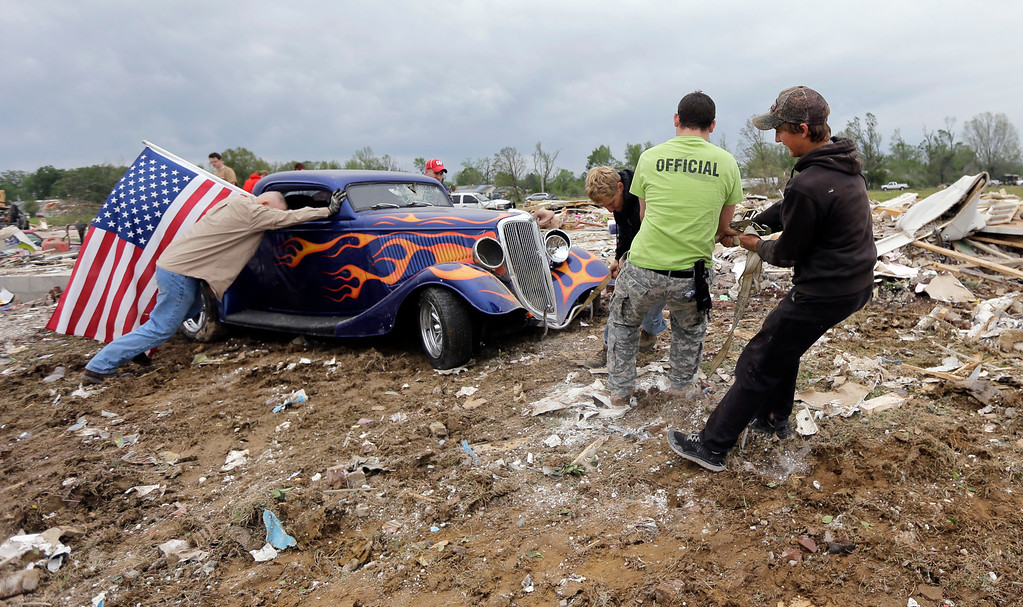 Description of . Friends and volunteers help remove Dan Wassom's 1934 Ford from the debris left by Sunday's tornado, Tuesday, April 29, 2014, in Vilonia, Ark.  (AP Photo/Eric Gay)