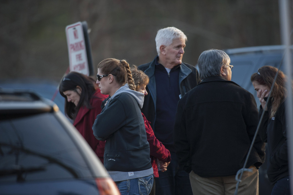 Description of . People stand on Dickson Street  near the scene of an elementary school shooting on December 14, 2012 in Newtown, Connecticut. According to reports, there are about 27 dead, 18 children, after a gunman opened fire in at the Sandy Hook Elementary School. The shooter was also killed.  (Photo by Douglas Healey/Getty Images)