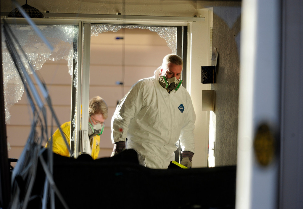 Description of . Investigators enter a town home at 16005 Ithaca Place in Aurora Saturday afternoon. The bodies of four people, including a gunman are dead at the scene following a standoff situation early Saturday morning. The Denver Post/ Karl Gehring